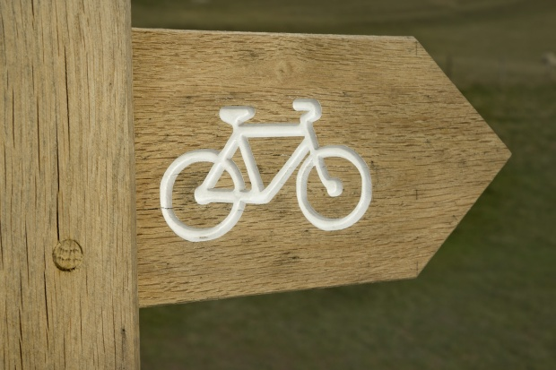 wooden sign with bicycle symbol, pointing to cycle path